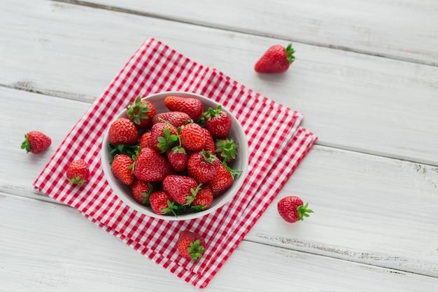 Tas de fraises fraîches dans un bol en céramique sur fond de bois blanc