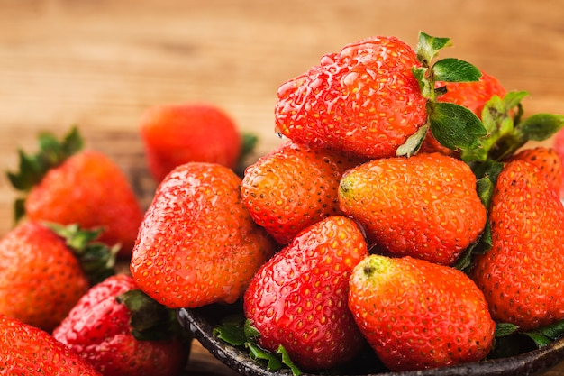 Tas de fraises fraîches sur fond de planche de bois