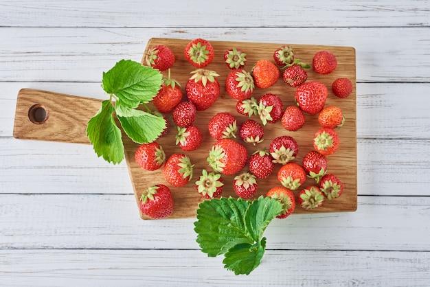 Tas de fraises fraîches avec planche à découper sur une vue de dessus en bois blanche. alimentation saine