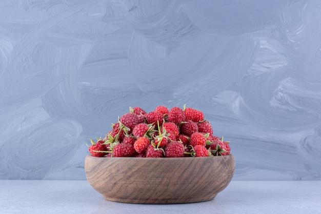 Tas de framboises délicieux dans un bol en bois sur fond de marbre. photo de haute qualité