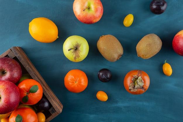 Tas de fruits frais entiers placés sur une surface bleue.