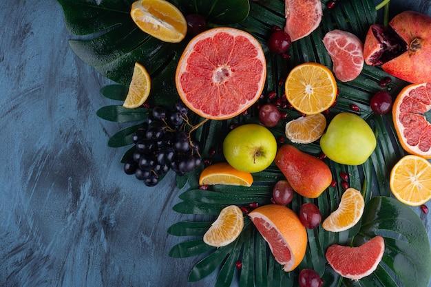 Tas de fruits frais juteux placés sur une table en marbre.