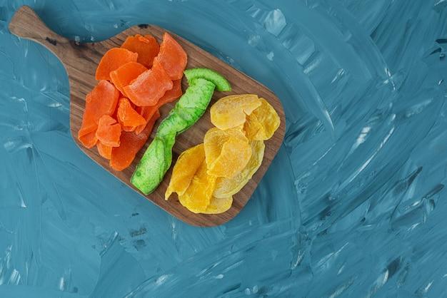 Tas de fruits tropicaux séchés placés sur une planche à découper en bois.