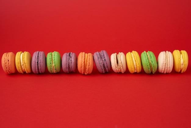 Tas de gâteaux de farine d'amande macarons cuits multicolores sur fond rouge