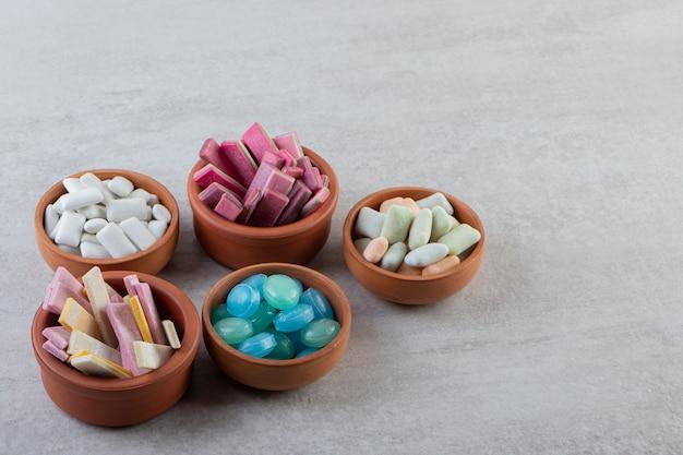 Tas de gommes dans des bols en bois sur une surface grise.