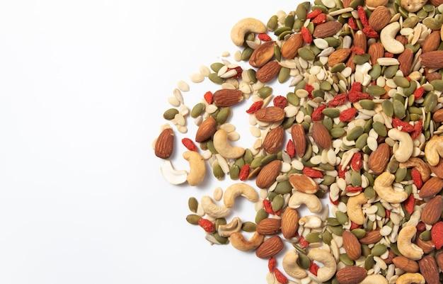 Tas de graines de céréales et de céréales biologiques mélangées sur fond blanc.