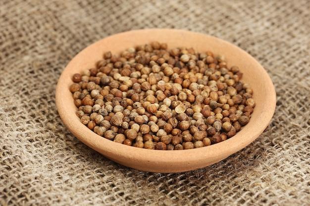 Tas de graines de coriandre dans un bol sur fond de toile close-up