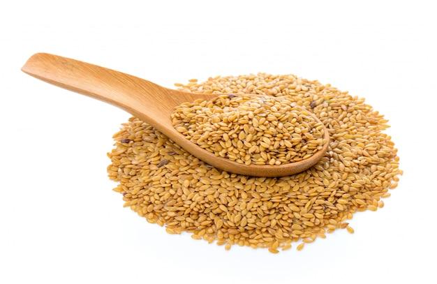 Tas de graines de lin dans une cuillère en bois isolé sur blanc isolé