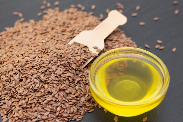 Un tas de graines de lin et d'huile de lin dans une cuillère en bois sur un fond noir en pierre. fond sombre concept de graines de lin.