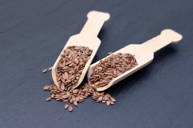 Un tas de graines de lin ou de lin dans une cuillère en bois sur pierre noire