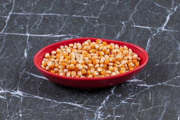 Tas de graines de maïs frais dans un bol rouge sur pierre noire.