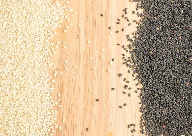Tas de graines de sésame noir et blanc sur fond de bois avec espace pour le texte