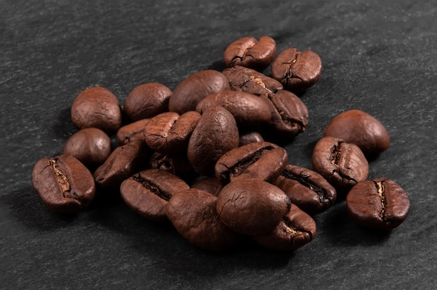 Tas de grains de café arabica sur un gros plan de fond noir foncé. prise de vue macro