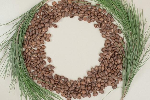 Tas de grains de café avec branche sur surface grise