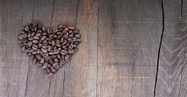 Tas de grains de café formant un cœur sur une planche rustique avec copie sapce à droite
