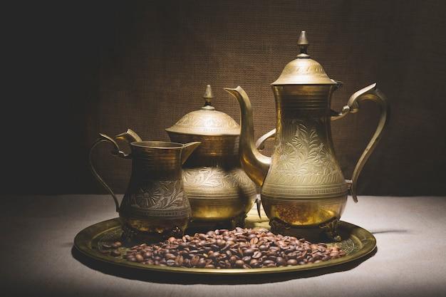 Tas de grains de café près de vieilles cafetières sur un plateau métallique