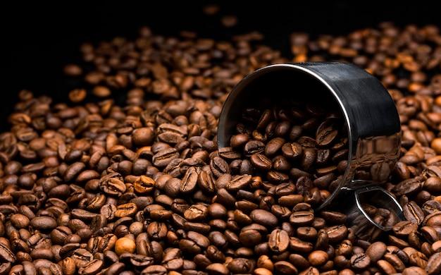 Tas de grains de café avec une tasse en métal, gros plan, fond sombre