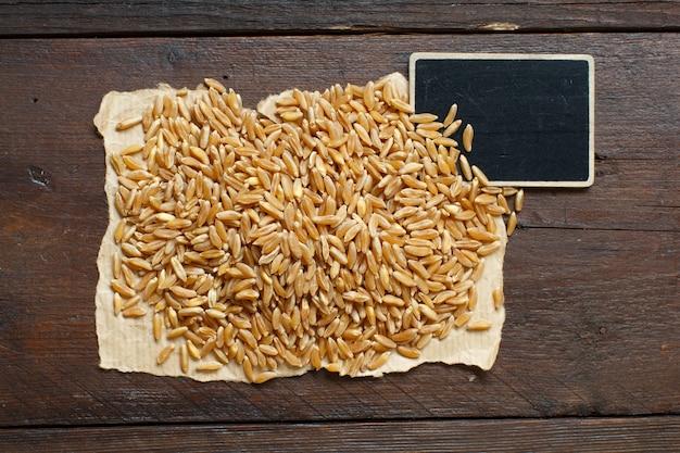 Tas de grains de kamut sur fond de bois avec petit tableau noir