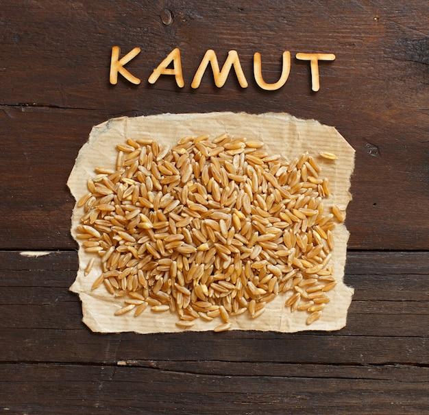 Tas de grains de kamut sur fond de bois vue de dessus