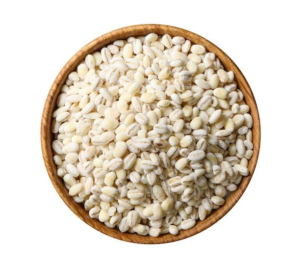 Tas de grains d'orge perlé dans un bol en bois close up isolé sur fond blanc. directement au-dessus