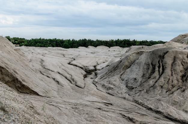 Tas de gravier avec des taches d'eau de pluie sur un fond de carrières de ciel bleu