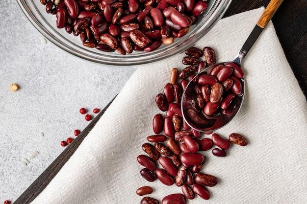 Tas de haricots crus dans une cuillère sur la table de la cuisine