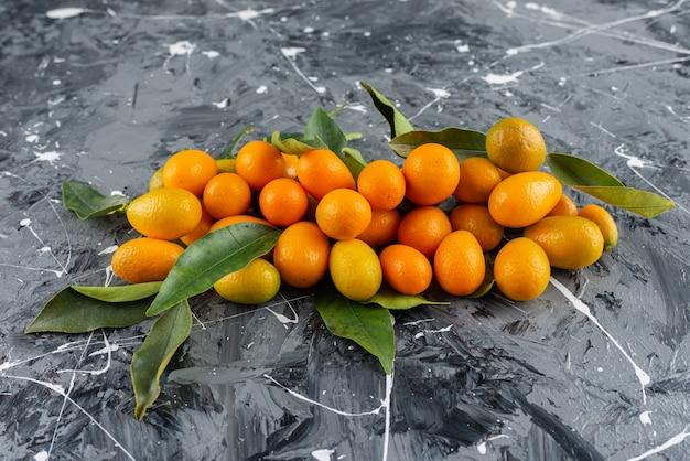 Tas de kumquats mûrs avec des feuilles vertes sur une surface en marbre.