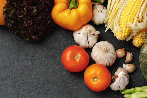 Tas de légumes frais sur fond noir, y compris les tomates, le maïs et l'ail