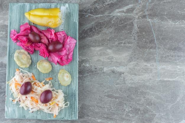 Tas de légumes marinés sur planche de bois.