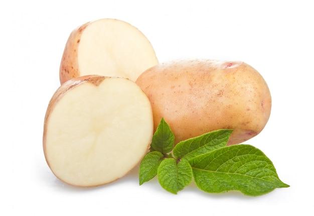 Tas de légumes mûrs de pommes de terre avec des feuilles vertes