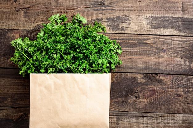 Tas de légumes verts frais, persil dans un sac en papier écologique sur fond de bois copy space