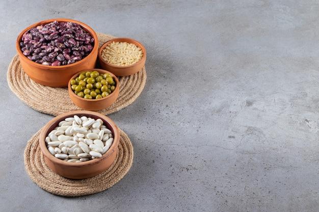 Tas de lentilles crues, haricots et riz sur fond de pierre.