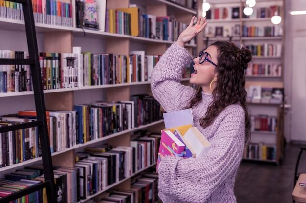 Un tas de livres. fille bouclée souriante en pull violet levant la main en signe de salutation tout en rencontrant quelqu'un