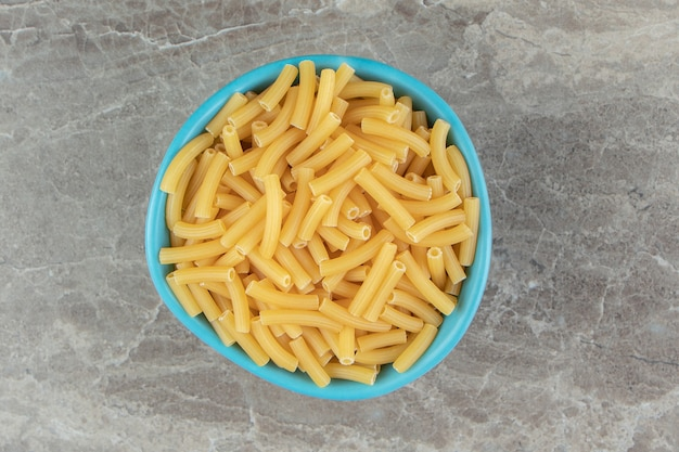 Tas de macaronis crus dans un bol bleu
