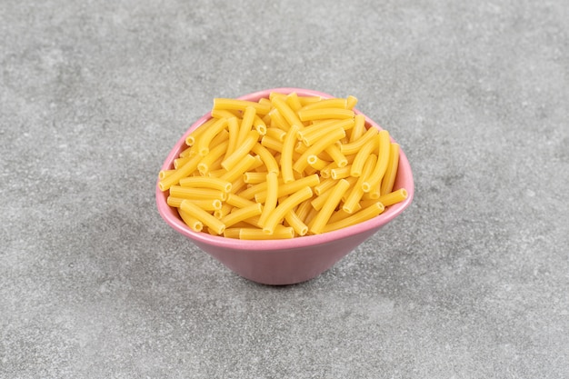 Tas de macaronis crus dans un bol rose
