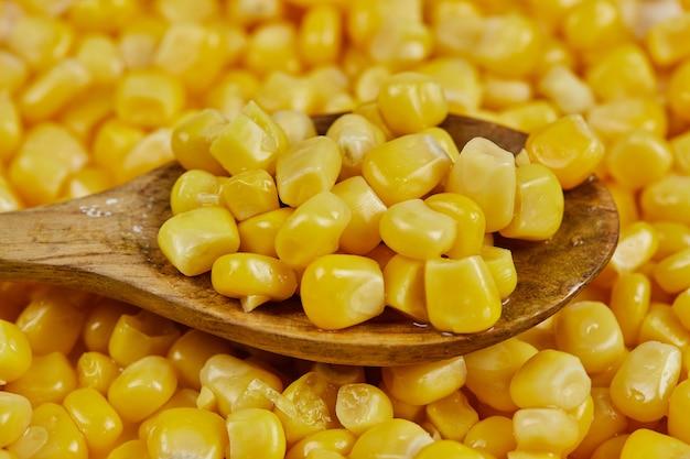Un tas de maïs doux bouilli avec une cuillère en bois sur une table blanche.