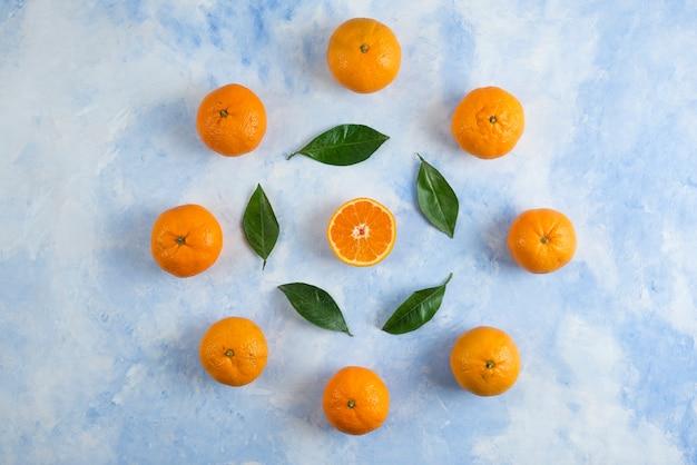 Tas de mandarines clémentines et de feuilles sur une surface bleue