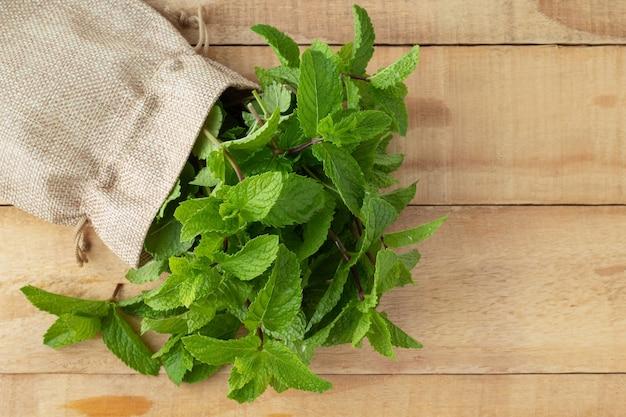 Tas de menthe aromatique fraîche en sac de jute sur table en bois, vue du dessus