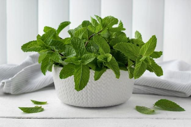 Tas de menthe fraîche biologique dans un bol sur une table en bois blanc