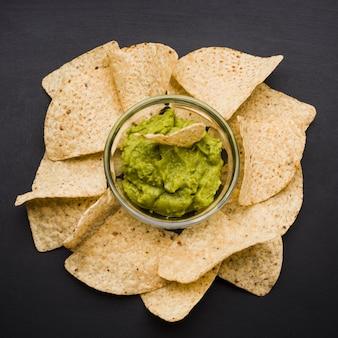 Tas de nachos et sauce dans un bol