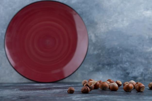 Tas de noisettes décortiquées bio avec plaque rouge vide.