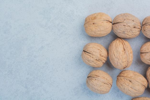 Tas de noix bio sur fond bleu. photo de haute qualité
