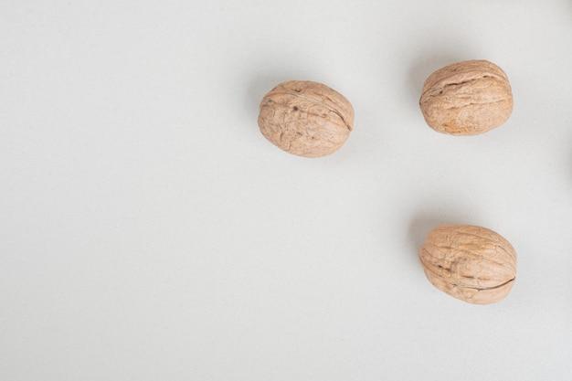 Tas de noix bio sur surface beige