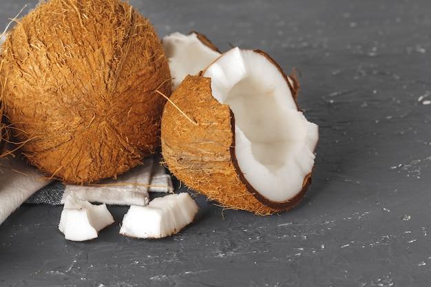 Tas de noix de coco cassées sur fond gris déchiré