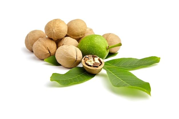 Tas de noix avec écrou non mûr sur des feuilles vertes fraîches isolées
