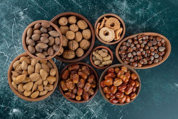 Tas de noix fraîches biologiques placés sur une table en marbre.