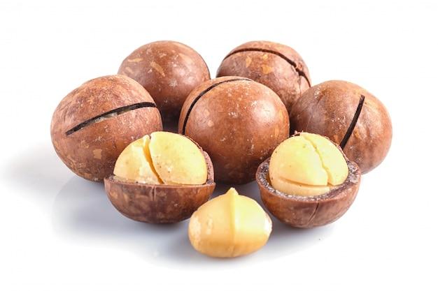 Tas de noix de macadamia avec coquille isolé sur blanc.