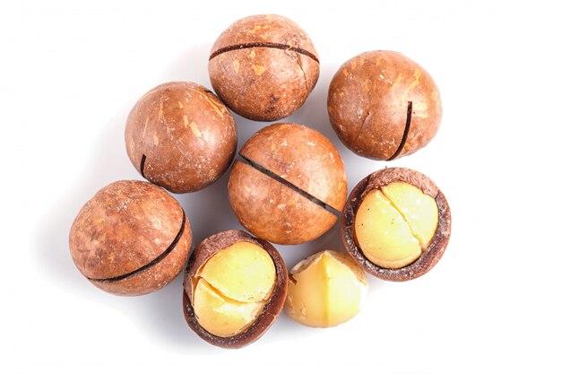 Tas de noix de macadamia avec coquille isolé sur fond blanc