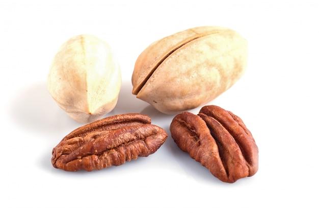 Tas de noix de pécan avec coquille isolé sur blanc.