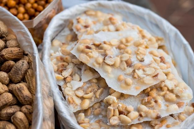 Un tas de noix rôties confites avec des arachides sur un poly-sac close up